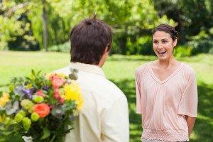 Frau ist sehr erfreut über den Heiratsantrag und über die Blumen, die Ihr Freund hinter dem Rücken versteckt