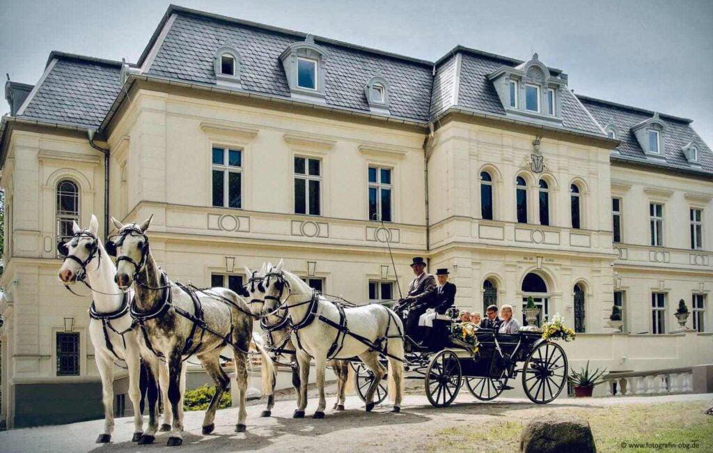 Schloss mit Pferdekutsche und Brautpaar